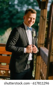 Portrait of a stylish bridegroom in a black suit in the open air