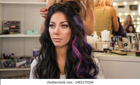 Portrait of stylish brunette. Girl makes an evening haircut in beauty salon. Work of hairstylistGirl with colorful dyed hair. Model with perfect healthy dyed hair. Bright stylish party look.