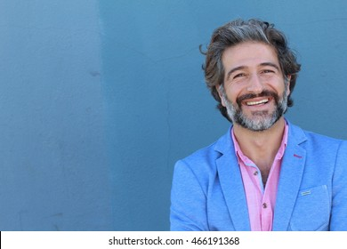 Portrait of stylish businessman smiling on blue wall background with copy space