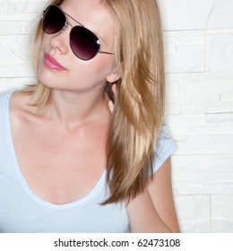 portrait of stylish casual girl with sunglasses in front of a wall