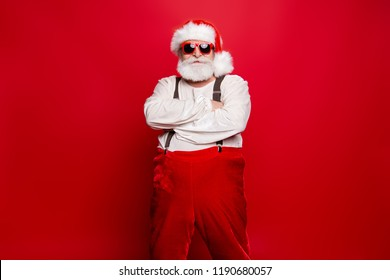 Portrait of stylish decisive content confident Santa wearing suit suspenders prepared ready for feast festive party promo sale promotion discount isolated over red background