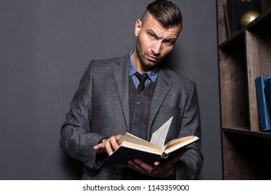 Portrait of stylish, elegant young man in suit with book. Young handsome man reads book