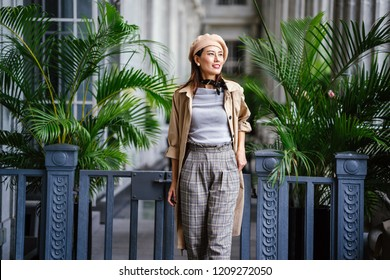 A portrait of a stylish and elegantly dressed Chinese Asian woman in a khaki trench coat and beret in a beautiful corridor in the city during the day. She is tall, slim and smiling brilliantly.