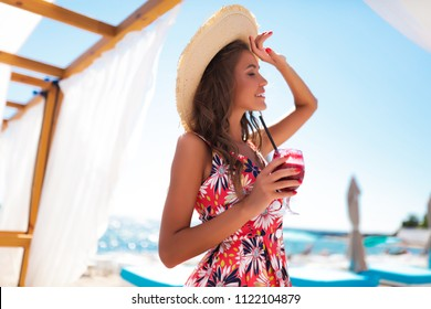 Portrait of stylish emotional girl wears straw hat and trendy summer flower dress posing beside exotic summer beach. Amazing blonde curly woman in white clothes standing on light,holding glass,teeth,