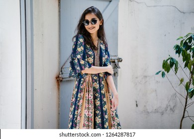Portrait of a stylish and fashionable Indian Asian woman in a summer dress and sunglasses.