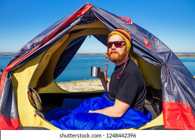 portrait of stylish ginger red-haired beard tourist man in a colorful hat made of yak wool from Nepal holding a mug of tea coffee in tent wrapped sleeping bag the background lake