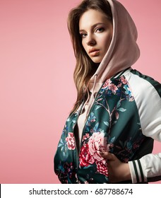 Portrait of a stylish girl in a bomb jacket with floral print standing on a pink background