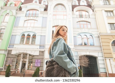 Portrait of a stylish girl in casual clothes poses on the backdrop of architecture, wearing a denim jacket, glasses and a backpack. Street tourist girl.