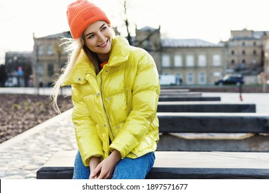 Portrait of  stylish girl wearing yellow puffer and orange knitted hat