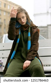 Portrait of a stylish girl who sits on a bench against a blurred background of outdoors. She is dressed in a boho style: a green jumpsuit and a long blue scarf.
