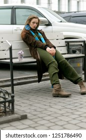 Portrait of a stylish girl who sits on a bench against a parking lot. She is dressed in a boho style: a green jumpsuit, a brown raincoat and a long blue scarf.