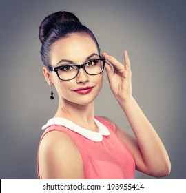 Portrait of stylish glamour lady wearing optical glasses. Young attractive retro dressed female model in spectacles posing in studio.