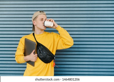 Portrait of a stylish guy in street clothes, caps and a fanny pack, standing on a blue background with a laptop in his hand and drinking coffee from a paper cup, looking sideways