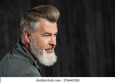 Portrait of stylish handsome adult man with beard. Man looking aside