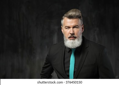 Portrait of stylish handsome adult man with beard. Man wearing black suit with blue tie and looking at camera