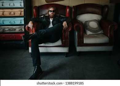 Portrait of a stylish handsome man on a leather sofa.