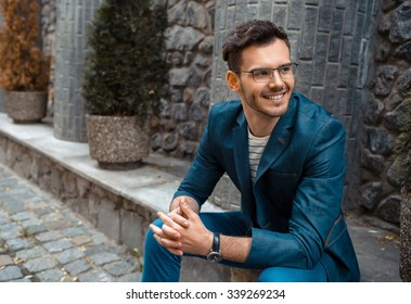Portrait of stylish handsome young man with bristle sitting on parapet outdoors. Man wearing jacket and shirt