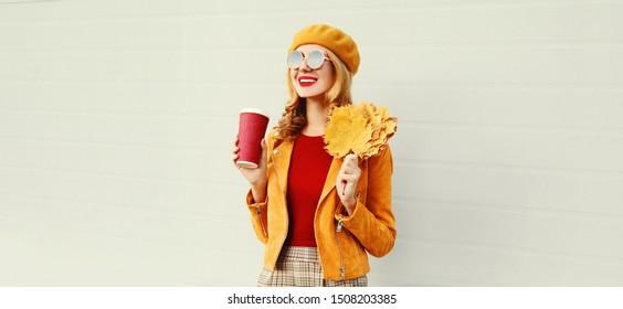Portrait stylish happy smiling woman with yellow maple leaves, coffee cup in french beret posing over gray wall background