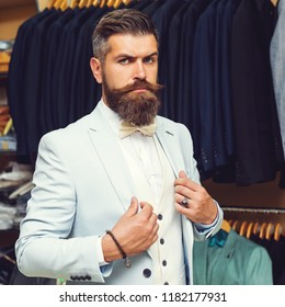 Portrait of stylish hipster brutal young man with red mustache, beard and beautiful hairstyle ready for event party while standing in clothing store.