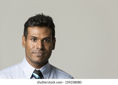 Portrait of a stylish Indian businessman standing in front of a light grey background. The photo has been composed so there is plenty of space for your message.