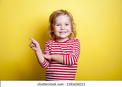 Portrait of stylish little girl with finger pointed up. Little child in striped shirt has idea. Kid isolated on yellow blackboard. Success, bright idea, creative ideas and innovation technology concep