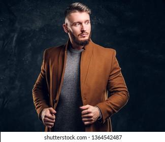 Portrait of a stylish male wearing the demi-season coat. Men's beauty, seasonal fashion. Studio photo against dark wall background