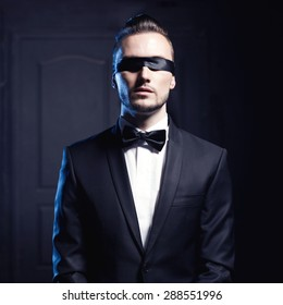 Portrait of stylish man in elegant black suit with blindfold