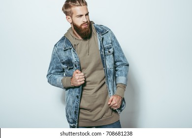 portrait of stylish man in jeans jacket looking away isolated on grey