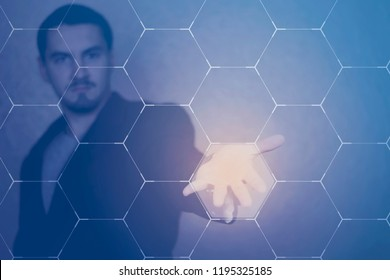 Portrait of stylish man pointing at transparent honeycomb. Virtual reality and innovation technology concept. pty space for text. Blurred background