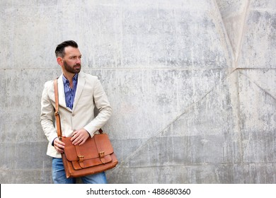 Portrait of stylish mature man standing against wall and looking away at copy space