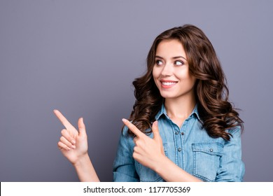 Portrait of stylish nice cute charming attractive cheerful magnificent adorable brunette caucasian girl with wavy hair in casual denim shirt, pointing aside up, isolated over grey background
