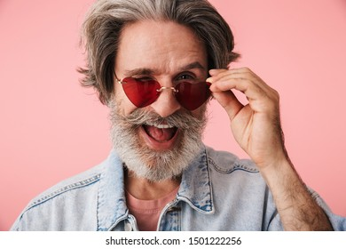 Portrait of stylish old man with gray beard wearing fashion sunglasses smiling and looking at camera isolated over pink background