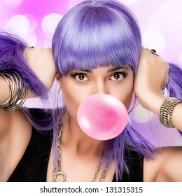Portrait of stylish party girl with purple wig and bubble gum