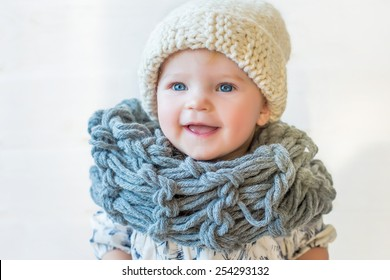 portrait of stylish pretty nice smiling baby girl in wool snood and hat, tall boots and modern dress staying on white background and wooden floor watching aside