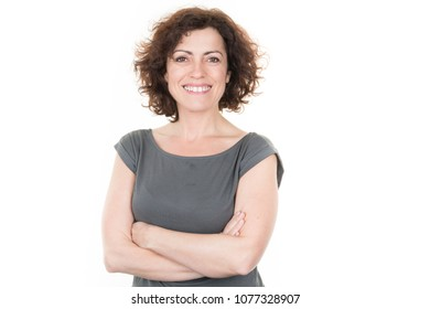 portrait of stylish pretty woman smiling in green grey t-shirt on white studio background, isolated, natural look, curly brown hair, crossed arms