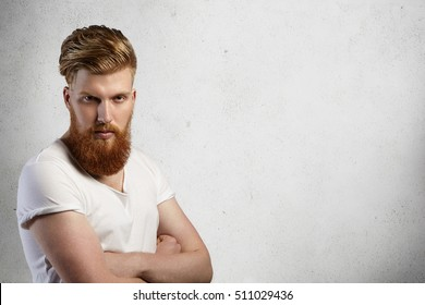 Portrait of stylish redhead hipster with fuzzy beard wearing white t-shirt with rolled up sleeves posing indoors with arms crossed, having sullen expression on his face. Isolated shot, horizontal