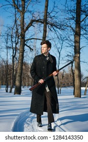 Portrait of a stylish serious man in coat with double-barreled shotgun on a sunny winter day. He is walking along snowy pathway carrying rifle in high ready position. Leafless trees on a background.