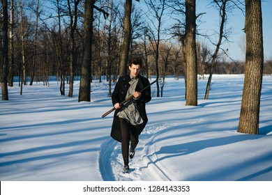 Portrait of a stylish serious man in coat with shotgun on a sunny winter day. He is walking along snowy pathway carrying rifle in high ready position. Picking up pace. Leafless trees on a background.