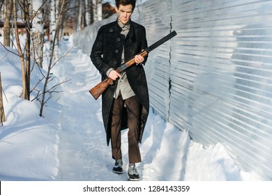 Portrait of a stylish serious man in opened coat with double-barreled shotgun on a sunny winter day. Brown breeches. He is walking along snowy pathway carrying his rifle in high ready position.
