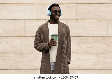 Portrait stylish smiling african man in wireless headphones listening to music with coffee cup wearing brown knitted cardigan and sunglasses on city street over brick wall background