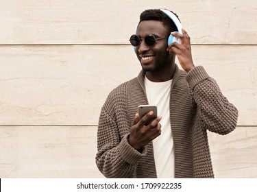 Portrait stylish smiling african man with phone in wireless headphones listening to music wearing brown knitted cardigan and sunglasses on city street over brick wall background