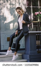 portrait of stylish smiling happy blond woman walking in street with backpack, curly hair, attractive, sunny, summer fashion trend, shirt, traveler, sunglasses, cheerful, backlight, positive,laughing