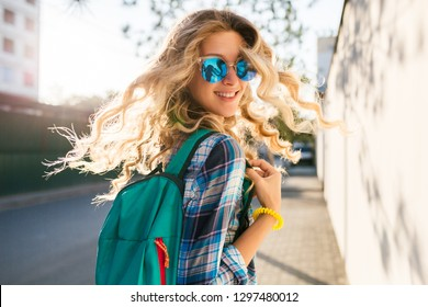 portrait of stylish smiling happy blond woman walking in street with backpack, curly hair, attractive, sunny, summer fashion trend