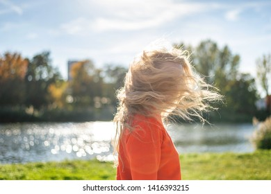 Portrait of stylish smiling happy blond woman walking in street with curly hair. attractive, sunny, spring fashion trend, traveler, cheerful, backlight, positive, laughing