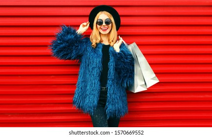 Portrait stylish smiling woman with shopping bags wearing blue faux fur coat, black round hat and sunglasses posing over red wall background