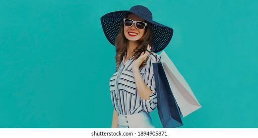Portrait einer stylischen Lächelin mit Einkaufstaschen, die einen schwarzen runden Sommerhut tragen, weißes gestreiftes Hemd auf blauem Hintergrund