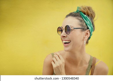 Portrait of stylish smily young woman wearing sunglasses outdoors on yellow background