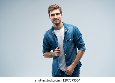 Portrait of stylish, stunning man in denim outfit standing over grey background