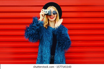 Portrait stylish surprised woman with retro camera taking picture wearing blue faux fur coat, round hat and sunglasses over colorful red wall background