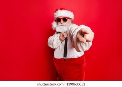 Portrait of stylish trendy happy joyful funky funny confident Santa pointing at camera prepared ready to feast festive party promo sale discount isolated over red background